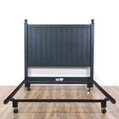 """This """"Ethan Allen"""" full-sized bedframe is featured in a wood with a navy paint finish. This contemporary style bed has a black metal base, round finial tops, and slatted headboard. Perfect for any bedroom! #contemporary #beds #headboard #sandiegovintage #vintagefurniture"""