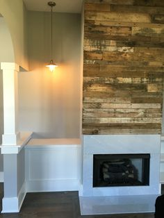 Pallet wood fireplace with chrome pendent light over a portrait hanging space. Superior Development, Llc. Nashville builder. Design by Jessica Powers.