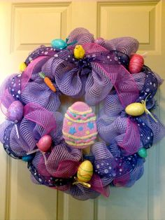 Hippity, Hoppity! Lavender non-metallic mesh with purple dotted and pink mesh ribbons, a large decorated egg surrounded by smaller glitter eggs, a fuzzy chick and a carrot!