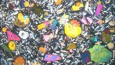Basalt from Stromboli, Colorful pyroxene crystals, white feldspar, black glassy matrix under polarized microscope.