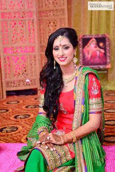 Indian bride wearing bridal lehenga and jewelry. #IndianBridalHairstyle #IndianBridalMakeup Mehendi Function by JD Photo Studios