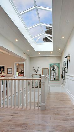 Coastal Home - A x custom skylight over the staircase atrium highlights the grandiose scale of the interior and brings even more light into home. Attic Renovation, Attic Remodel, Coastal Homes, Coastal Cottage, Coastal Farmhouse, Farmhouse Plans, Luxury Interior Design, Stairways, My Dream Home