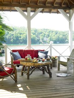 Boathouse Deck Adirondack chairs and midcentury bentwood seating, as well as a coffee table crafted by a local artisan, furnish this summer cabin's deck. The blue-and-white pillows are from Restoration Hardware. Read more: Porch and Patio Decorating Ideas - Outdoor Room Ideas - Country Living