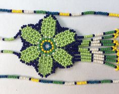 Beautiful Huichol necklace with a bag integrated on the back of the flower. Finished in beautiful colors. Piece representing religious and cultural meanings of the Huichol.  All pieces are unique pieces Huichol being handmade products, however we can make a similar product if you need more than one piece