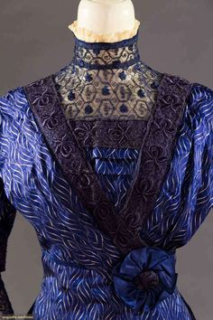 "2 SILK DAMASK AFTERNOON DRESSES, 1910-1915 Both 1 piece w/ lace insertion high necks & surplice bodices: 1 navy blue silk damask w/ pattern of cubes & white spiral print, very op-art, B 32"", W 24"", L 55"", (stain on right H) excellent & 1 pink in window pane damask, bows to back, B 34"", W 25"", L 57"", (areas silk worn & some splits) fair; t/w 1 pale blue silk & lace over-dress."
