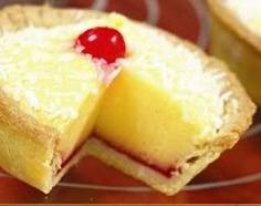 Manchester tart with custard filling - Manchester tart is a traditional English baked tart consisting of a shortcrust pastry shell, spread with raspberry jam, covered with a custard filling and topped with flakes of coconut and a Maraschino cherry.