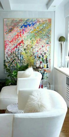 Beckoning club chairs, colorful art & a well stocked bar cart