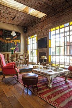 Living con gran ventanal de vidrio repartido y techo de ladrillo expuesto en una casa reciclada del Bajo San Isidro.: