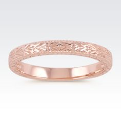 A vintage-inspired detailing covers this wedding band and is outlined by milgrain for an attention grabbing look! This ring is crafted of quality 14 karat rose gold and measures 2.5mm wide. Add this ring to any attire or to complement an existing engagement ring.