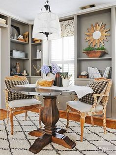 The square desk felt too formal, so it was swapped for a round table, which functions as a workspace and a serving area for entertaining. The cabinets were painted a light gray, which causes them to recede and allows accessories to shine./