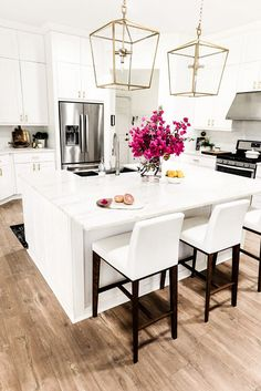 White kitchen with marble countertops and gold light fixtures