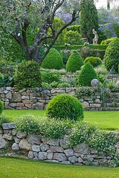 Stone walls, slope, tiered landscape, and evergreens. This will look this fabulous all year round!
