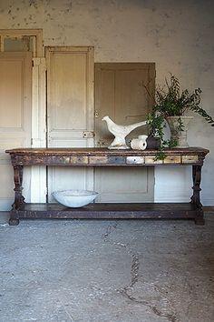 ボルドー地方カウンターテーブル-antique french counter table 両サイドの装飾が独特。7,oooに及ぶボルドー地方のシャトーの内の一つで使われた、おそらく当時は壁に付けコンソール的役割を担ったかと思われるテーブル。その後、近年迄の巡り合いはと言うと、天板に残る小さな穴やペンキ飛沫の跡から推測するとアートオブジェを製作するアトリエの台とされたのかも。壮観の10個抽き出しはテーブル片側だけの仕様、全てオリジナルの状態で現存していてくれた事が嬉しい。総オールドパイン材で19世紀初頭まで遡る古い時代の品。ショップカウンターとして、また、エントランス入って直ぐのメインテーブルとして多様に。
