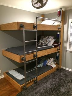 The triple bunk beds my engineer husband designed for our three sons who share a bedroom!! It feels like a work of art in the room. As you can see from the pic, the bookshelf wasn't complete when I took the picture. We were able to find vintage explosion proof globes & hardware which was the finishing touch! They look amazing when turned on. Each boy has their own shelves, light switch and outlet for their bed! They LOVE it! All 6 of us were on the middle bunk at once this week!!!