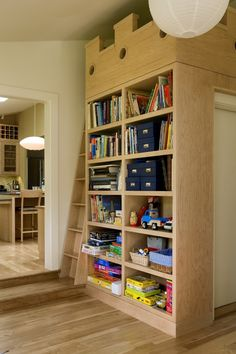 This secret loft is a private space for little ones within the public spaces on the first floor. The shelves at the bottom of the ladder are filled with games, toys and books they can bring up with them.