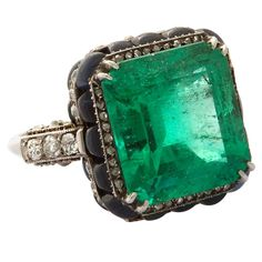 Art Deco Emerald Ring in Platinum, enhanced with Diamonds and Calibré Cabochon Sapphires, Boucheron Paris, circa 1920. Emerald of 15.4cts.