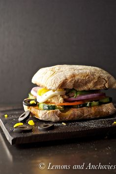 """""""A pan bagnat is a Nicoise salad in sandwich form.  Tuna, olives, a hard-boiled egg, onions and other vegetabes are bathed in an anchovy vinaigrette (pan bagnat means 'wet bread').  It is a great make-ahead type of sandwich–sealing it in plastic wrap for at least two hours allows the flavors to meld–but it is also wonderful enjoyed immediately."""""""