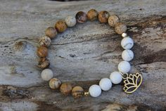 White Lotus bracelet by Wanderbird. Made from picture jasper, howlite and lotus charm. The lotus is the symbol for new beginnings and leaving behind negativity. White Lotus, Yoga Bracelet, Jasper Stone, Jewelry Design, Unique Jewelry, Stone Beads, Beaded Bracelets, Trending Outfits, Handmade Gifts