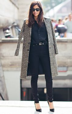 A black button-down shirt is tucked into a belted pair of skinny jeans, an animal print coat, Ray-Ban sunglasses, and pointed-toe black pumps
