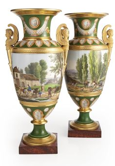 A PAIR OF PARIS PORCELAIN VASES CIRCA 1825 each painted around the ovoid body with a continuous view of a countryside depicting figures at various pursuits, the trumpet-shaped neck, shoulder and lower body decorated with neoclassical patarae or palmettes on the green ground between gilt borders, affixed on either side with a gilt winged herm handle.