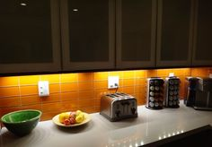 Lush glass subway tile Poppy orange glows with under cabinet lighting at night. www.modwalls.com