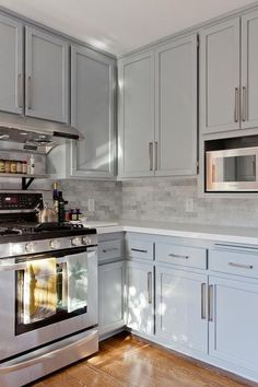 Beautiful kitchen features gray shaker cabinets paired with engineered white quartz countertops and a gray marble linear tiled backsplash.