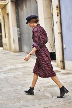 cap, print dress with rolled cuffs and ankle boots.