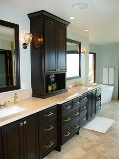 Sleek dark cabinetry is the focal point in this traditional master bath. A custom cabinet on an angled wall accentuates the room's length and maximizes storage. Polished nickel fixtures and hardware add a touch of elegance, as do hand-blown sconces and a freestanding tub.