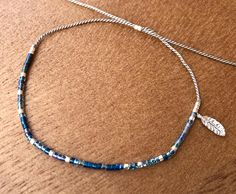 Minimalist silver feather charm bracelet with blue seed beads (glass) and gray silk cord. Follow us: https://www.instagram.com/cocoloccajewelry ******************************* ******************************* This is a delicate item due to its materials, even though the silk cord is very