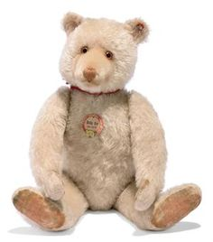 A STEIFF WHITE DICKY BEAR, (5335,2), jointed, mohair, orange and black glass eyes, inset short mohair muzzle, brown stitching, printed velvet pads, inoperative squeaker, FF button, remains of red cloth tag and chest tag, circa 1932 --16in. (40.5cm.) high (some general wear and thinning of mohair, pads discoloured)