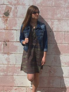 Camo is in and it's hot!!! This all Tied Up tank dress has simple tie detail on neckline and pockets. We paired it with our denim jacket for cooler days
