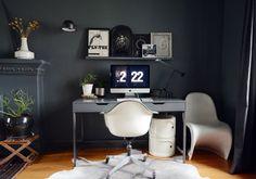 Home Office elegante. Parede cinza escuro, luminárias industriais e móveis brancos contemporâneos no escritório