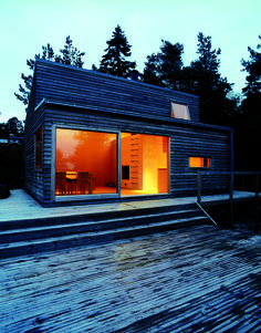 Large sliding glass doors allow daylight to fill the living room. Smaller windows are placed in the kitchen area and the sleeping loft. The exterior is clad in heart pine which needs very little up-keep and is known for its strength and hardness.
