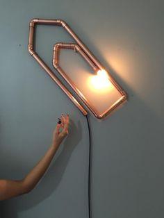 A divertida e inusitada luminária CLIPS é feita em tubos de cobre e pode ser fixada com um simples parafuso na parede. Lixada a mão, recebe uma camada de verniz protetor, garantindo seu brilho por um londo período de tempo.