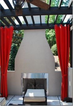 Outdoor curtains with an outdoor fireplace.
