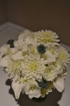 Classic white bridal bouquet with dahlias, lisianthus, calla lilies, and scabiosa pods. Fleurish Floral Designs