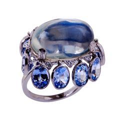 An exceptional 20.60 carat cabochon moonstone is set in platinum and accented with ten oval-shaped blue sapphires totaling 10.09 carats. The sapphires are bezel-set in platinum with a milgrain edging. There are ten round brilliant cut diamonds accenting the ring and totaling 0.22 carats.