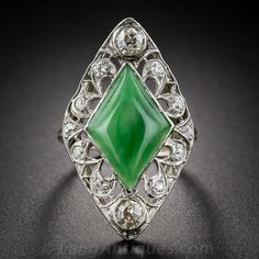 A rare, wonderful and highly distinctive natural jade and diamond dinner ring from the early-twentieth century. The sizable (almost 1 and 1/4 inches long) Edwardian ring features a lozenge-shape jadeite (measuring 11/16 by 7/16 inch), displaying a mottled Kelly-green color, bezel set in a consummate openwork diamond frame, crafted in platinum and transitioning into a yellow gold ring shank (which may have been replaced at a later date). Langantiques.com
