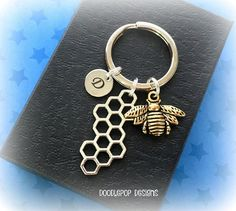 Personalised honeybee keyring with a honeycomb charm (double sided) and laser engraved initial. PLEASE ASK IF YOU REQUIRE MORE THAN ONE INITIAL. EACH EXTRA INITIAL IS £1.50. Style: Personalised bee and honeycomb keychain. Size: keyring is 62mm (approx. 2 & 1/2 inches in length). including ring and charms. Materials: Antique silver and gold plated charms, 10mm stainless steel, laser engraved initial, 25mm silver tone split ring. ALL JEWELLERY AND ACCESSORIES ARE LEAD AND NICKEL FRE...