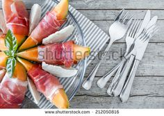 Closeup overhead view of half plate with melon slices wrapped in prosciutto and mozzarella slices. - stock photo
