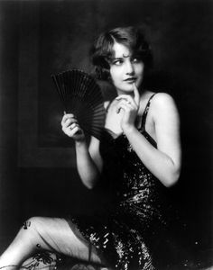 "Future Hollywood star Barbara Stanwyck, three-quarter length portrait, seated, turned to the left, holding fan. Photograph by Alfred Cheney Johnston ""between 1920 and 1930"", but more likely between 1922 (when Stanwyck, aged 15 and still named Ruby Stevens, became a Ziegfeld Girl), and 1926 (when she moved on to greater things)."