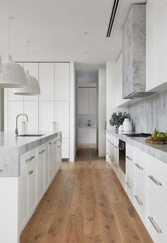 Modern Hamptons-style kitchen with timber flooring and marble benchtops