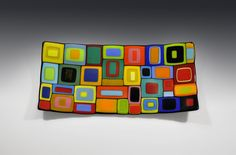 Rectangular Carnival Bowl by Helen Rudy. Striking colorful fused glass bowl. Lots of colored squares and rectangles of hand cut glass layered on top of each other like a large sandwich. The glass is first kiln-fired to fuse each component into a single piece of glass. The glass is slumped into its final form. Each piece is unique. Exact patterning and colors may vary slightly. This piece is food safe, functional and very stunning. Looks great with food or on display as a piece of art. Hand…