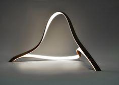 ilia estudio interiorismo: Una escultórica lámpara con dos tiras de madera, diseño de John Procario