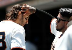 San Francisco Giants' Hector Sanchez (29) fixes San Francisco Giants' Michael Morse (38) hair in the dugout after Morse scored a run against the Miami Marlins in the first inning at AT&T Park in San Francisco, Calif. on Sunday, May 18, 2014. (Nhat V. Meyer/Bay Area News Group)