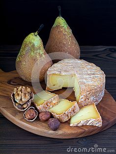 Soft washed-rind cheese, walnut, hazelnuts and pears on the wooden board