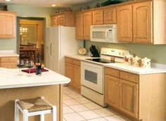 traditional light wood kitchen cabinets with white appliances. this