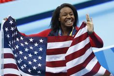 Gold medallist USA's Simone Manuel wave her national flag during the medal ceremony of the Women's 100m Freestyle Final during the swimming event at the Rio 2016 Olympic Games at the Olympic Aquatics Stadium in Rio de Janeiro on August 11, 2016.   / AFP / Odd Andersen