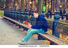 Young American man wearing blue sweatshirt, fashionable destroyed jeans, gray casual shoes, sits on long bench at Central Park, New York in autumn day, looks down, reads red book. Filtered effect.