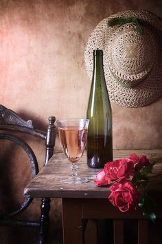 http://nikolay-panov.pixels.com/products/pink-wine-and-roses-nikolay-panov-art-print.html • Rustic still life photography with glass of pink wine, green bottle and small bouquet of red roses on vintage wooden table and straw hat hanging on wall in country in daylight in summer